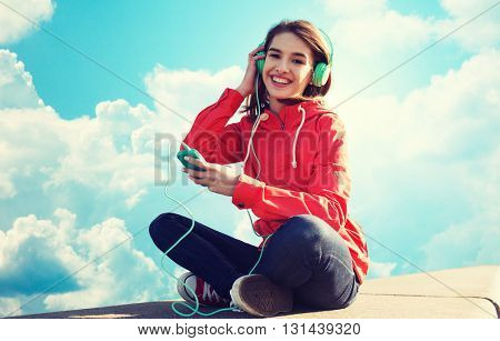 technology, music and people concept - smiling young woman or teenage girl with smartphone and headphones listening to music outdoors over blue sky and clouds background