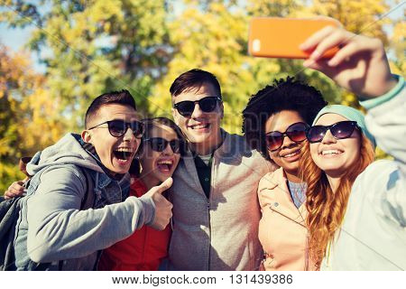 people, season, friendship and technology concept - group of smiling teenage friends taking selfie with smartphone and showing thumbs up over autumn park background