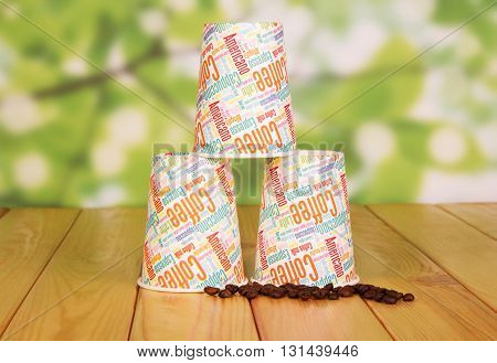 Disposable paper cups and coffee beans on abstract green background.