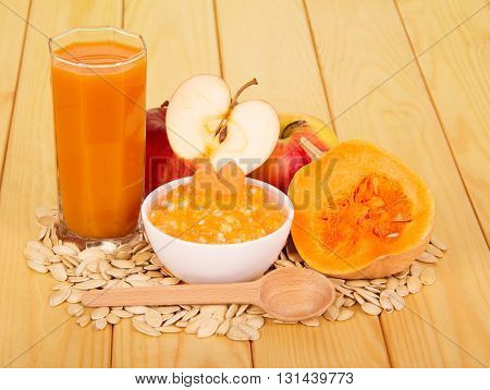 A bowl of pumpkin puree, a glass of juice, apples, seeds and spoon on a background of light wood.