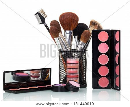 Cosmetic brushes, lip gloss, blush, eye shadow and powder isolated on white background.