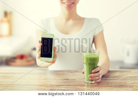 healthy eating, diet, detox, technology and people concept - close up of woman with smartphone green juice sitting at wooden table over kitchen background