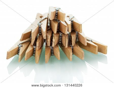 Pile of wooden clothespins isolated on white background.