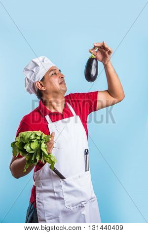 indian male chef cook holding green spinach leaves and egg plant in hand, asian male chef holding fresh vegetables