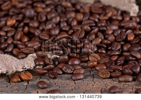 Black coffee beans on a wooden surface