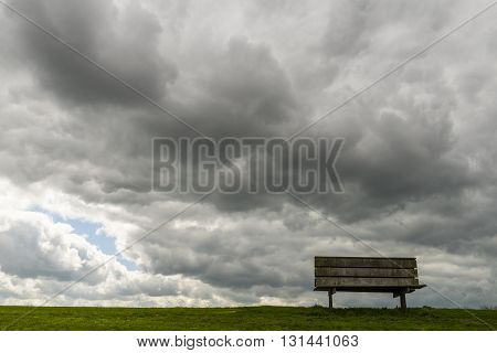 Bench on a dike in Friesland with dark rain and storm clouds. Netherlands.