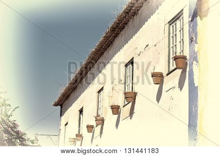 Shabby Facade of Portuguese House Decorated with Flower Pots Retro Image Filtered Style