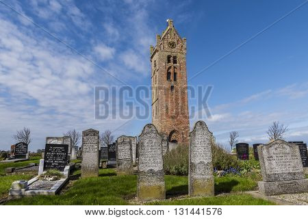 Firdgum The Netherlands - April 18 2016: Church tower and graveyard of Firdgum in Friesland in the Netherlands early spring.
