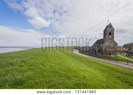 Wierum The Netherlands - April 18 2016: Church of Wierum with Waddensea dike in Friesland in the Netherlands.