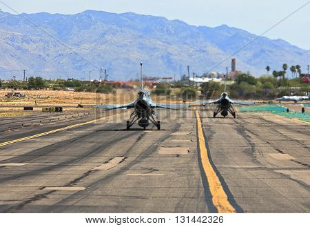 Taxiing on runway behind F-16 fighter jets