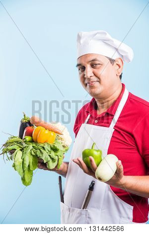 indian male chef holding fresh vegetables in hand, asian male cook chef standing with vegetables, isolated over blue background