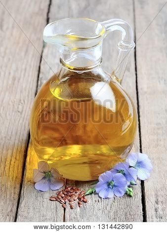 Flax oil with blue flowers on wooden texture