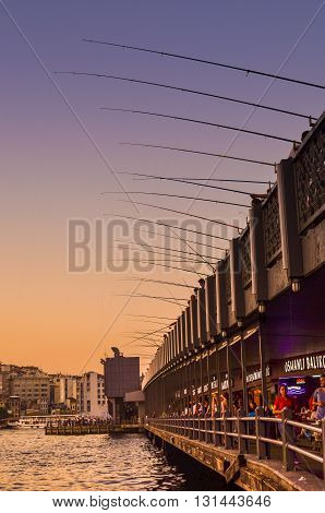 ISTANBUL, TURKEY - AUGUST 12, 2016: Fishing poles on Galata Bridge in Istanbul in lovely sunset sky colors