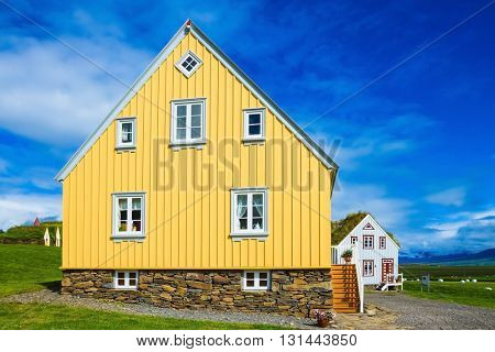 The charming rustic rural house on green lawn. Travel to Iceland