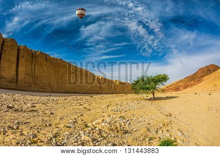 The route starts in the scenic Black Canyon. Huge multi-colored balloon over stone desert near the seaside resort of Eilat