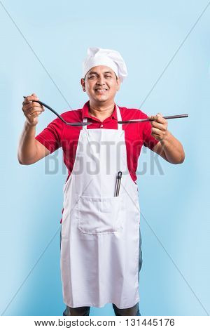 Young Chef Holding spoon skimmer and wooden spoon Isolated On blue Background