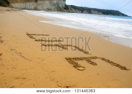 Etched word written in beach sand by the sea