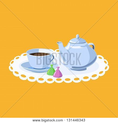 Cup of tea on a saucer teapot and chocolates on a white lacy napkin.