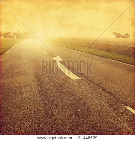 Grunge image of country road with arrow sign on asphalt.