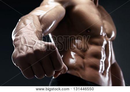 Handsome muscular bodybuilder shows his fist and vein, blood vessels. Studio shot on dark background.