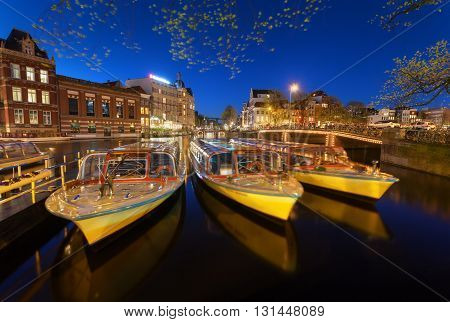 Night Cityscape With Traditional Old Houses And Boats In Amsterdam