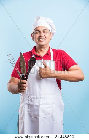 Multitasking is a chefs game. Closeup portrait of handsome indian cook holding a wooden culinary spoon and soup ladle and knife while standing over blue background with copy space, asian male chef