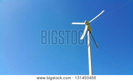 White water pumping wind mill on blue sky background