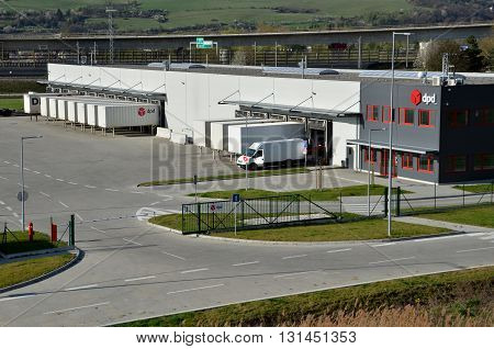Dolny Hricov Slovakia - April 13 2016: Modern logistics center of international parcel delivery company DPD white van and trailers standing on ramp