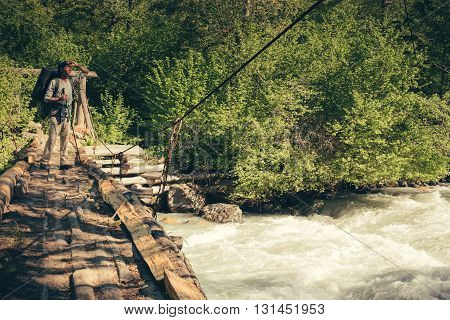 A Man Traveling With Backpack Hiking On Bridge Over River. Travel Lifestyle Concept.