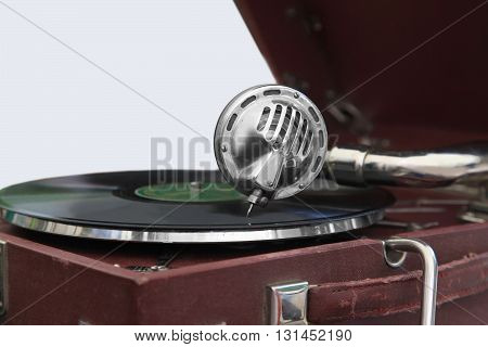 Old gramophone with a wooden body and a spring drive