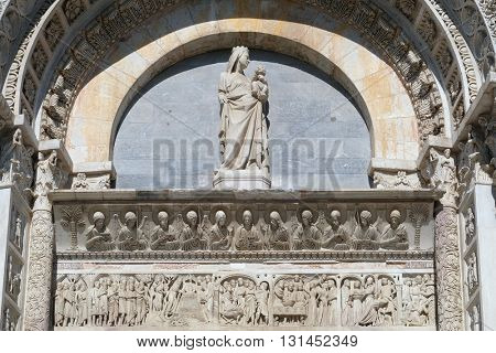 PISA, ITALY - JUNE 06, 2015: Virgin Mary with baby Jesus above Entrance Door of Cathedral Church Baptistery in Pisa, Italy. Unesco World Heritage Site, on June 06, 2015