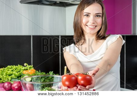 Young beautiful woman standing in the kitchen offers at arm's length three tomatoes. Tomatoes in focus face blurred