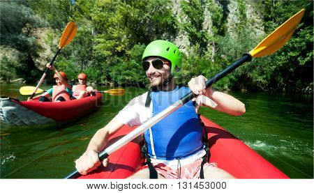 A male in red inflatable canoe having fun in calm waters of a river. Another one with two behind.
