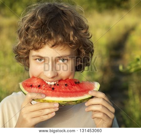 happy teenager eating watermelon in the garden
