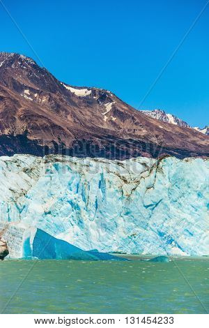Massive glacier descends into the water.  The picturesque  shore of Lake Viedma. In the water ice-floes, broken away from glacier