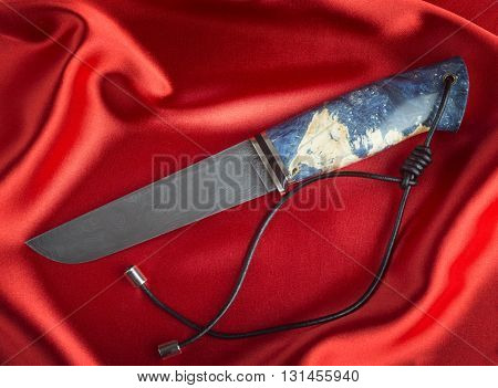 Hunting knife handmade close up on red satin.