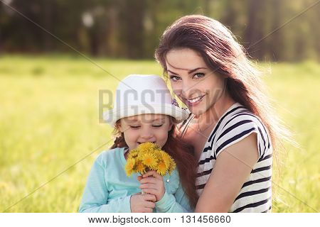 Beautiful Young Mother Embracing Her Cute Daughter With Yellow Bright Flowers On Summer Background