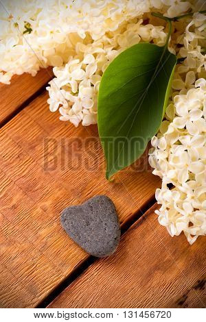 Vertical photo with several flowers of lilac. Single green leaf on lilac blooms. White lilac blooms. Flowers with heart shaped stone placed on wooden board. Grey stone next to flowers.