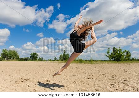 Contemporary dance. Woman in passionate dance pose on beach. Modern dance in beautiful pose outdoors. Girl doing splits in jump against the sky, clouds.