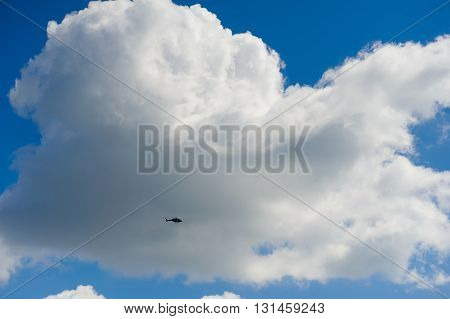 Silhouette helicopter on a background of huge clouds in the sky