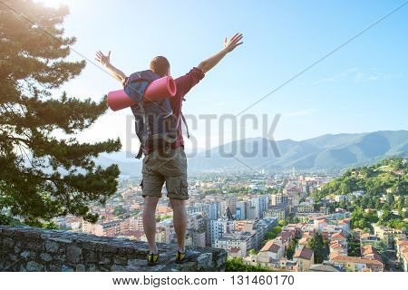 young traveler standing with open arms on the city landscape