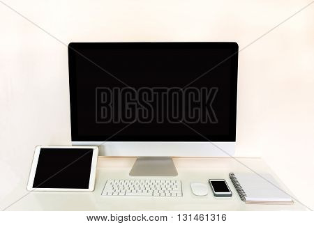 computer tablet and mobile phone with blank black screen and accessories on table with off white background modern electronic gadget device