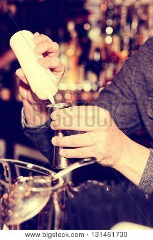 Bartender is adding secret ingredient in a cocktail, toned image