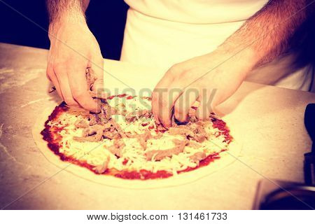 Making of a meat pizza, professional kitchen, old, toned image