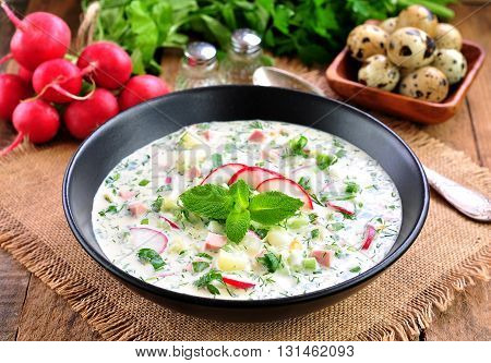 Cold summer soup with radish, cucumber, dill, parsley boiled eggs and potatoes. Russian traditions.