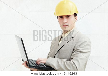 Industrial theme: constructor standing at a building site.