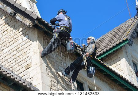 Cascais, Portugal - March 08, 2016: Abseiling building maintenance workers at work.