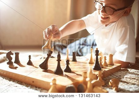 boy in white shirt playing chess and makes a move