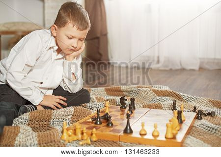 sad boy lost a game of chess sitting in front of a chessboard