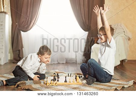 two boys are playing chess. boy wins chess. boy loses at chess